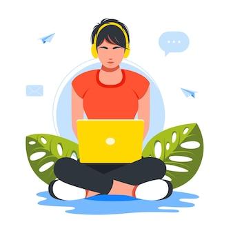 노트북과 헤드폰을 사용하여 바닥에 로터스 위치에 앉아 있는 비즈니스 우먼. 집에서 로터스 위치에 있는 노트북으로 헤드폰을 끼고 일하는 여자 프리랜서, 온라인 학습, 재택 근무 개념