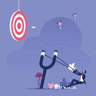 Businessman aiming with a slingshot to target