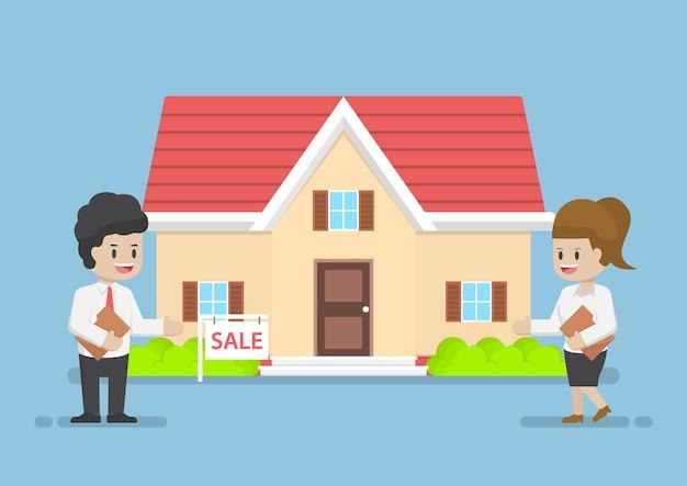 Бизнесмен и бизнес-леди, представляя дом на продажу