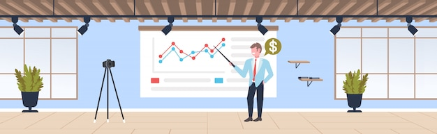 Businessman blogger explaining charts financial graph business man recording online video with camera on tripod presentation blogging concept modern office interior full length horizontal
