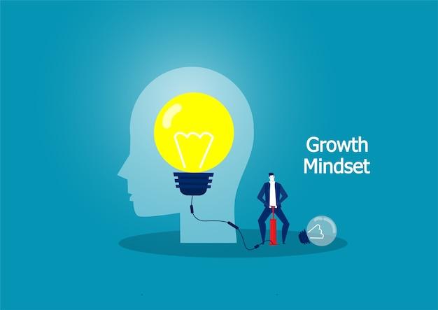 空気ポンプで電球を吹いているビジネスマン。成長の考え方の概念。