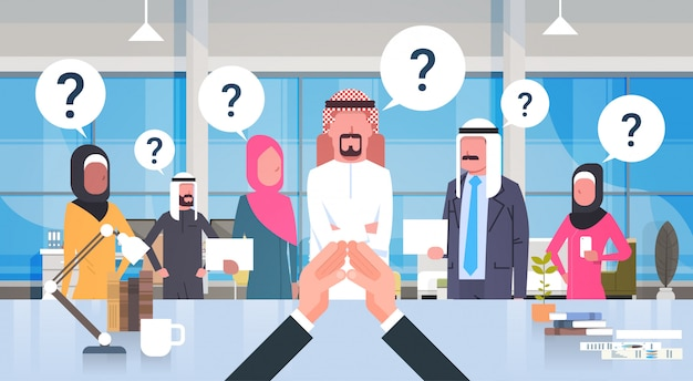 Businessman boss looking at brainstorming business team of arab people with questiion mark sitting at desk, leader with group of saudi businesspeople in modern office
