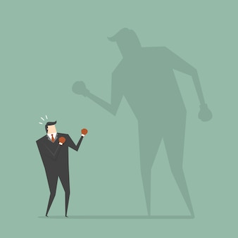 Businessman boxing with a shadow