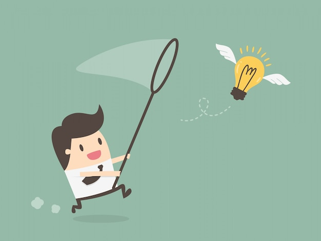 Businessman chasing flying light bulb