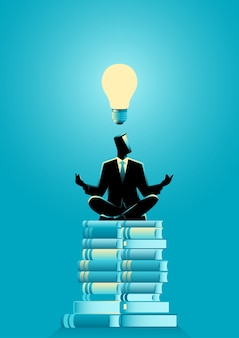 Businessman doing yoga on books pile