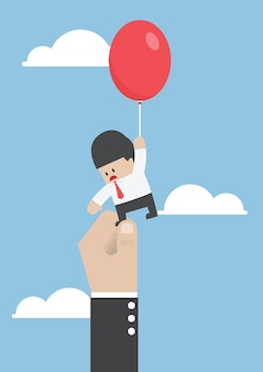 Businessman flying away with balloon