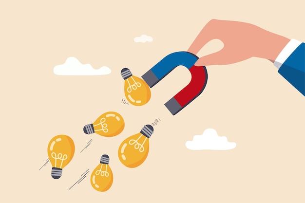 電球ランプのアイデアを磁化または描画するための磁石を持っているビジネスマンの手。
