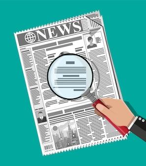 Рука бизнесмена удерживая увеличительное стекло над газетой с названиями и фото
