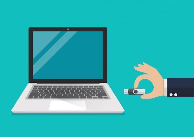 コンピューターのラップトップを接続するusbフラッシュドライブを持っているビジネスマン手