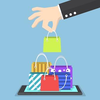 タブレットで買い物袋を選ぶビジネスマン手