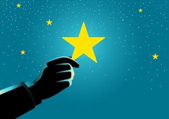 Businessman hand picking up a star