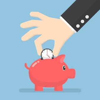 Businessman hand putting clock into piggy bank