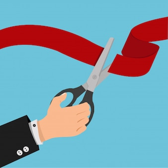 Businessman hand Red ribbon  with black scissors