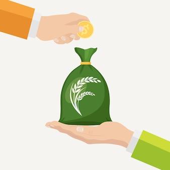 ビジネスマンの手は穀物の袋を握り、作物を売って、穀物を買う。農業収入、アグリビジネス
