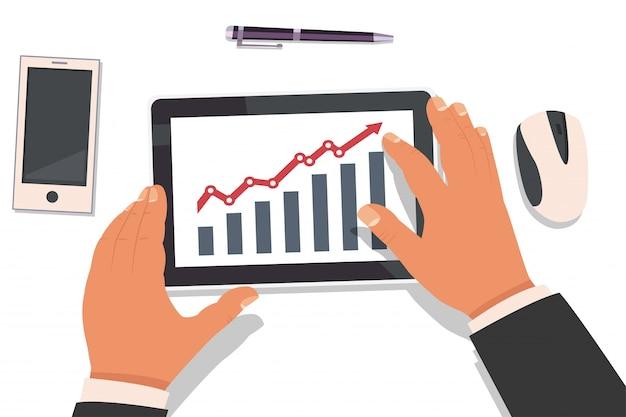 タブレットを保持し、市場分析統計のグラフを操作するビジネスマンの手