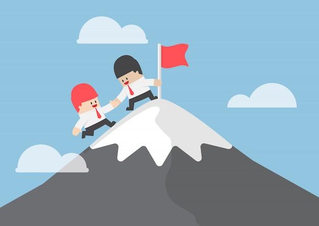 Бизнесмен помочь своему другу, чтобы достичь вершины горы