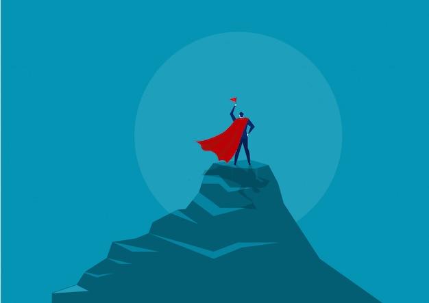 Герой бизнесмена держа красный флаг и стоя на верхней части горы под солнцем.