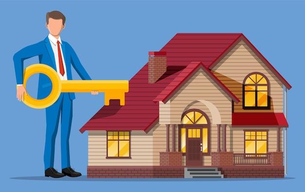 家の建物の近くに大きな鍵を保持しているビジネスマン