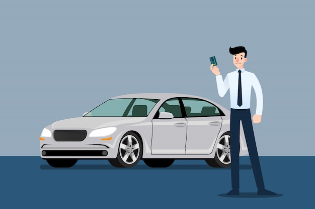 Businessman holding credit card in front of car.
