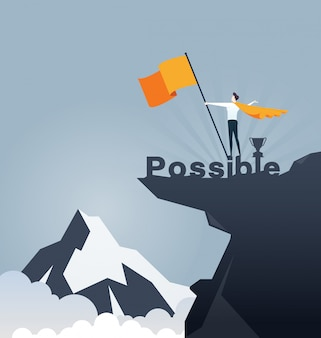 Businessman holding flag and standing on top mountain.