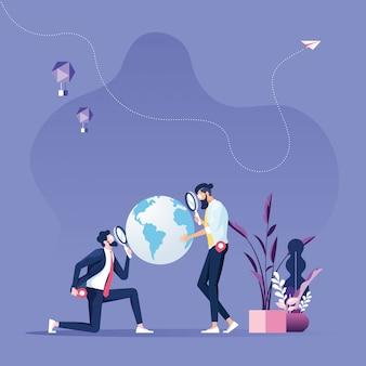 Бизнесмен держит увеличительное стекло над картой мира
