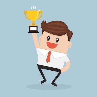 Businessman holding winning trophy.