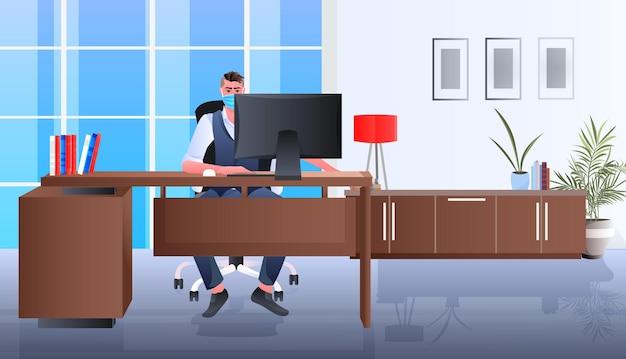職場に座っているマスクのビジネスマン オフィスで働くビジネスマン コロナウイルス検疫コンセプト 水平全長図