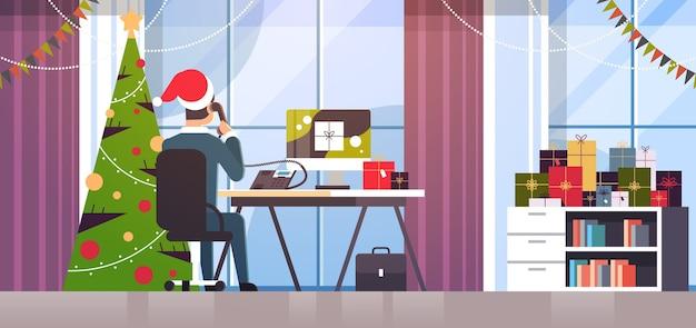 サンタクロースの帽子をかぶったビジネスマンが電話で話している職場で話しているビジネスマンギフトボックスでモニターを見て冬の休日のお祝いのコンセプトモダンなオフィスインテリア