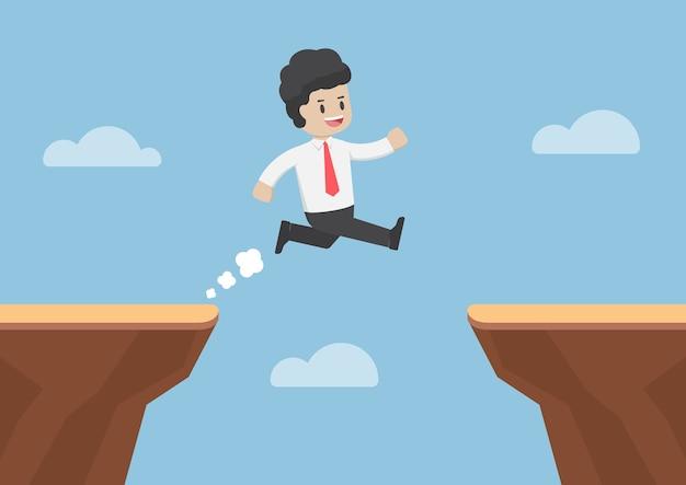 Бизнесмен прыгает через пропасть между утесами