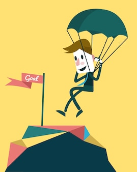 Businessman landing to the goal with parachute.