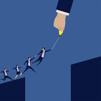 Бизнесмен лидер помогает другим прыгать через разрыв.