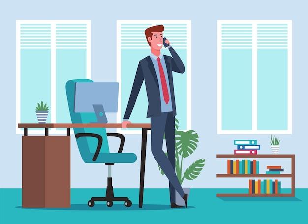 テーブルに寄りかかって、オフィスで電話で話しているビジネスマン