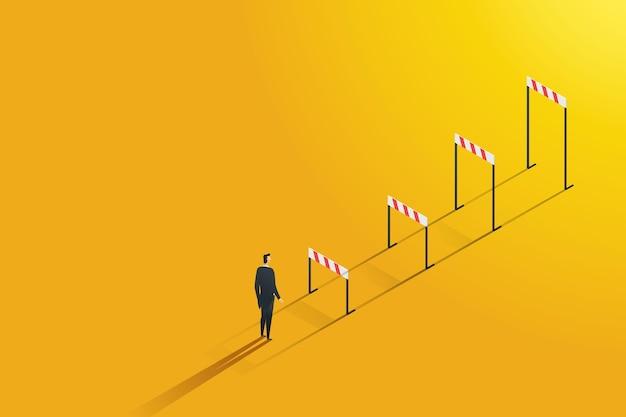 ビジネスマンは、障害を飛び越えて克服することを野心的な、より高いキャリアの障壁を見ています