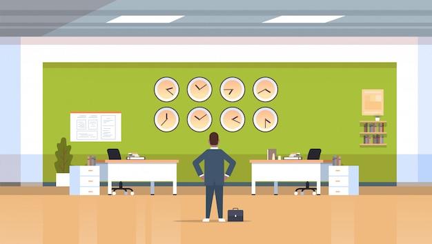 Бизнесмен смотрит на стену с часами разных городов тайм-менеджмент срок концепция современный офис интерьер горизонтальный вид сзади мужской персонаж полная длина