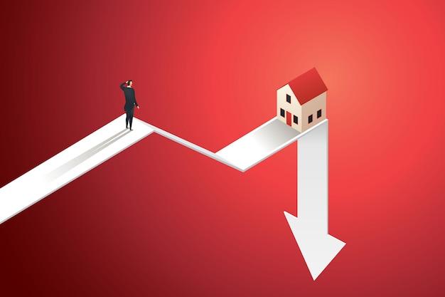 ビジネスマンは、矢じりが落ちている不動産市場のグラフを見ます