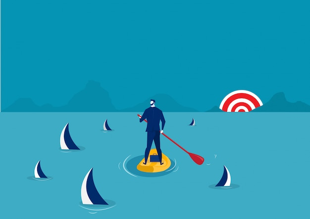 Businessman paddle boarding in the suit with island surrounded by sharks.
