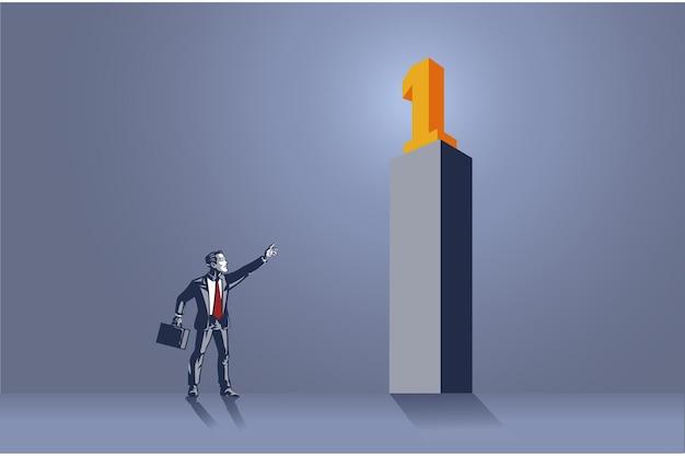ナンバーワンブルーカラーコンセプトの高い記念碑を指すビジネスマン