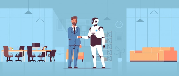Businessman and robot handshaking during meeting agreement partnership artificial intelligence futuristic mechanism technology modern office interior