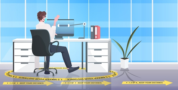 Businessman sitting at workplace desk social distancing coronavirus epidemic protection