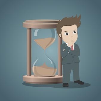 Бизнесмен, стоя и мышление с песочные часы или песочные часы для управления временем.