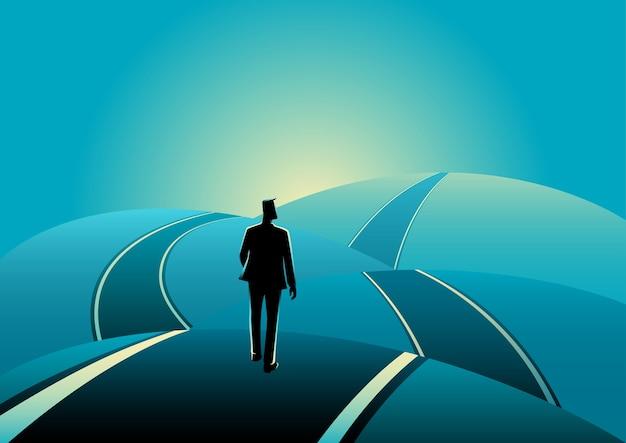 Businessman standing on the asphalt road over the hills