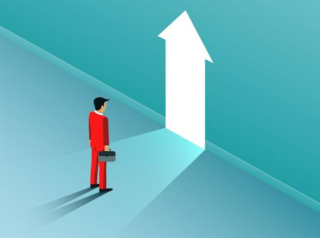Businessman standing in front of open arrow door with bright light