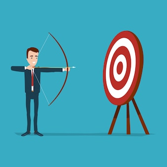 Businessman stands and aims from bow to target. round goal with red circles on three legs