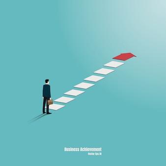ビジネスマンはグラフの上部を見つめるように立っています。目標、成功、野心、達成、および課題のビジネスコンセプトの矢印。