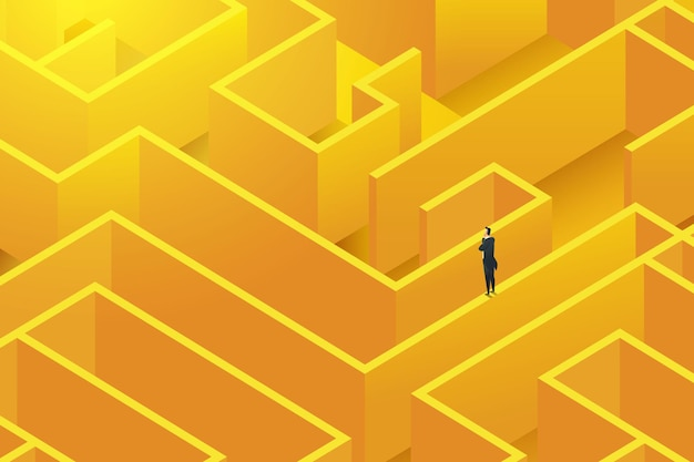 Businessman stands on wall a large complex maze to find solutions to challenges decision
