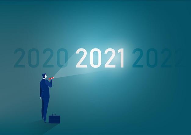 Бизнесмен стоит с фонариком к цели 2021 года