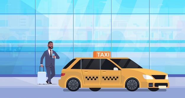 黄色のタクシーの都市交通サービスコンセプト全長水平近く荷物とフォーマルな服装でストリートビジネスの男性にモバイルアプリ注文タクシーを使用するビジネスマン