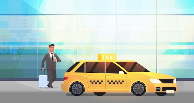 黄色のタクシーの都市交通サービスの近くの荷物とフォーマルな服装でストリートビジネスの男性にモバイルアプリ注文タクシーを使用するビジネスマン