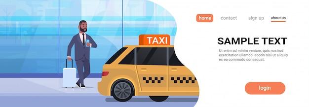 黄色いタクシー都市交通サービスコンセプト全長水平コピースペース近くの荷物を持つストリートビジネスの男性にモバイルアプリ注文タクシーを使用するビジネスマン