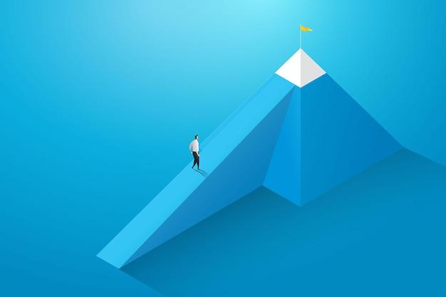 ビジネスマンは山の頂上への道で彼の目標に向かって歩いた